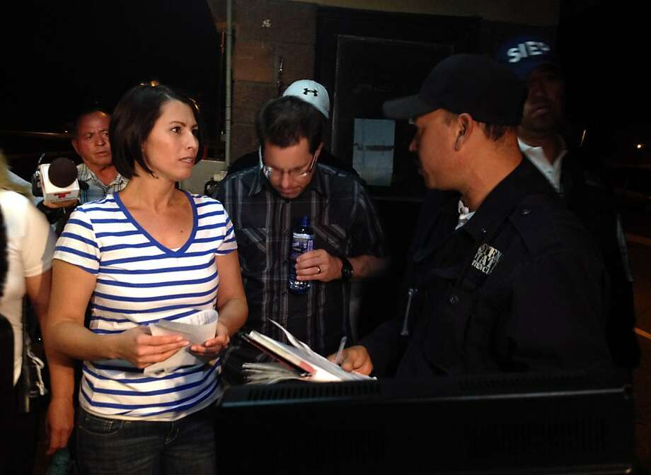 Yanira Maldonado, 42, left, accompanied by her husband, Gary, center, speaks to an official after being released from a prison on the outskirts of Nogales, Mexico late Thursday, May 30, 2013. Maldonado, jailed in Mexico on a drug-smuggling charge, was released after court officials reviewed her case. She was arrested by the Mexican military last week after they found nearly 12 pounds (5.4 kilograms) of pot under her seat on the commercial bus traveling from Mexico to Arizona. (AP Photo/Cristina Silva) Photo: Cristina Silva, Associated Press