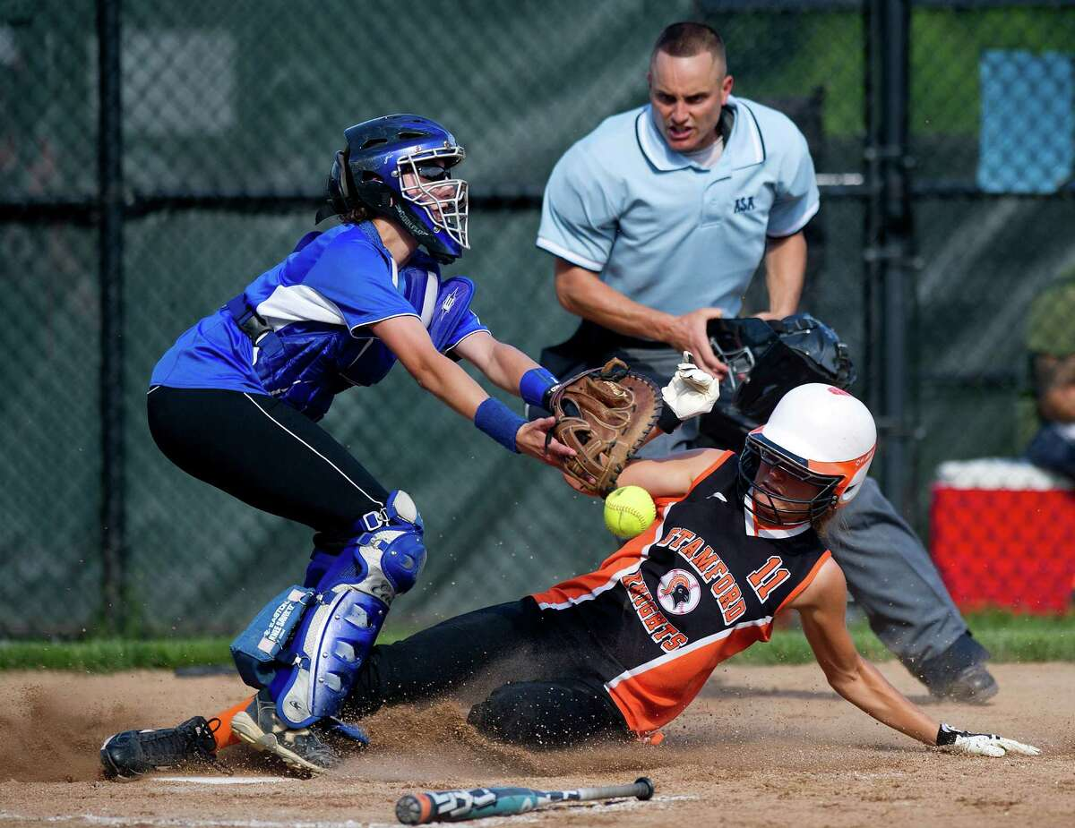 Stamford's Clare Kaptinski scores a run as Darien's Rebecca DeMaio reaches for the ball during Friday's FCIAC quarterfinal softball game at Darien High School on May 31, 2013.