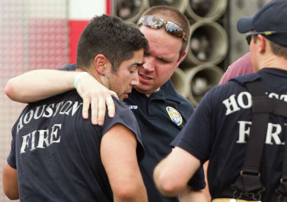 Houston firefighters embrace near the scene of a fatal five-alarm fire at a motel on the Southwest Freeway Friday, May 31, 2013, in Houston. Photo: Brett Coomer, Houston Chronicle / © 2013 Houston Chronicle