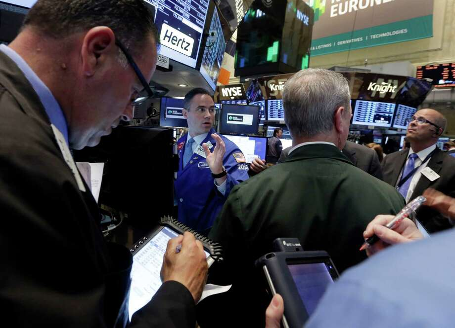 In this  Tuesday, May 28, 2013, photo, Traders gather at the post that handles Hertz on the floor of the New York Stock Exchange.  Stock futures slumped on the final trading day of May, with new data showing that consumers pulled back from their breakneck spending pace in April. (AP Photo/Richard Drew) Photo: Richard Drew