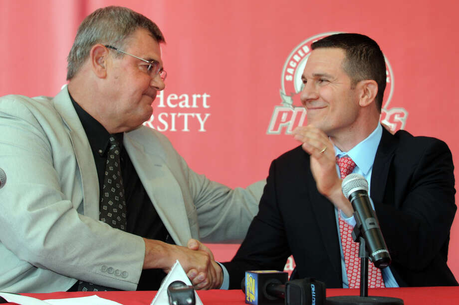Former Sacred Heart University men's basketball coach Dave Bike, left, shakes hands with new coach, Anthony Latina, during a press confernece in the McMahon Center on campus in Fairfield, Conn., May 30th, 2013. Photo: Ned Gerard / Connecticut Post