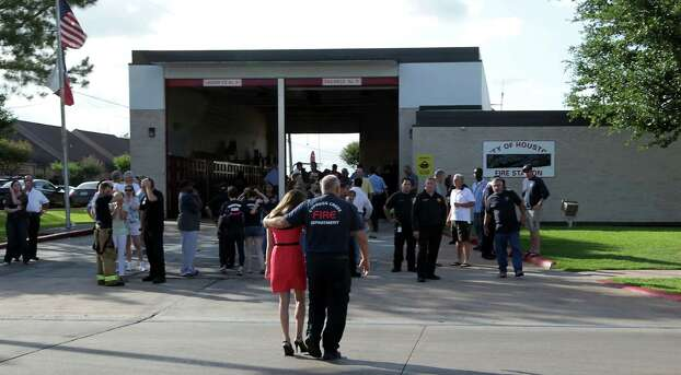A man consoles a woman outside HFD station 51 after the loss of several firefighters who died today fighting a five alarm fire at a restaurant fire Friday, May 31, 2013, in Houston. Photo: James Nielsen, Houston Chronicle / © 2013  Houston Chronicle