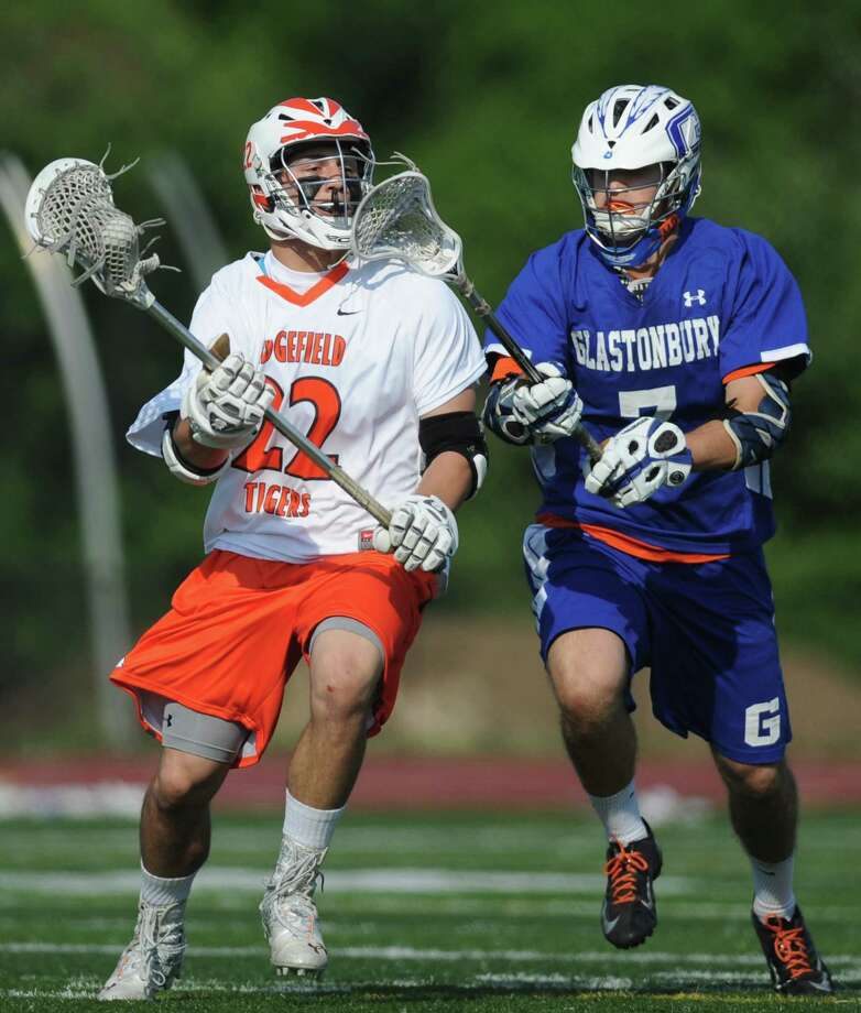 Ridgefield's William Bonaparte, left, battles by Glastonbury defender Chase Conway during No. 1 Ridgefield's 14-5 win over No. 8 Glastonbury in the quarterfinal round of the high school boys lacrosse Division L State Tournament at Ridgefield High School in Ridgefield, Conn. on May 31, 2013. Photo: Tyler Sizemore / The News-Times