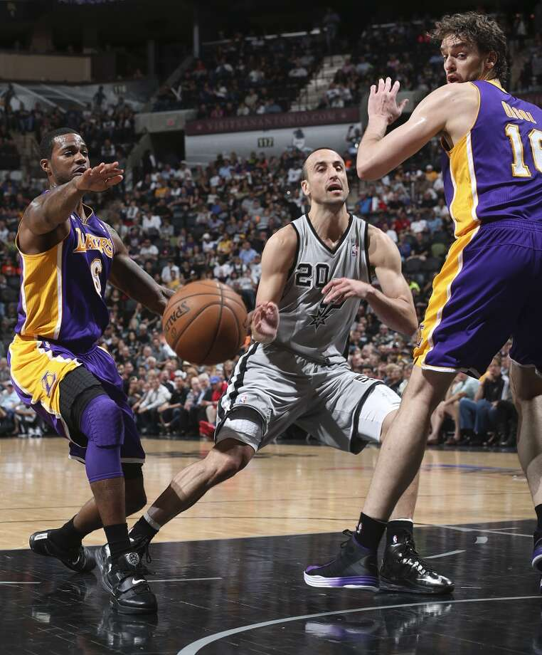 San Antonio Spurs' Manu Ginobili passes the ball through Los Angeles Lakers' Earl Clark, left, and Pau Gasol during the first half of game 1 in the first round of the NBA Playoffs at the AT&T Center, Sunday, April 21, 2013.