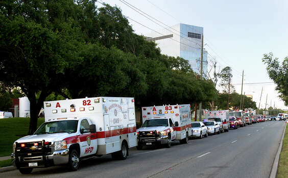 A procession lead by ambulances carrying the bodies of the four fallen firefighters drive to the Forensic Center of Harris County to be examined, Friday, May 31, 2013, in Houston. The firefighters died fighting a five-alarm fire at the Southwest Inn earlier in the day. Photo: Cody Duty, Houston Chronicle / © 2013 Houston Chronicle