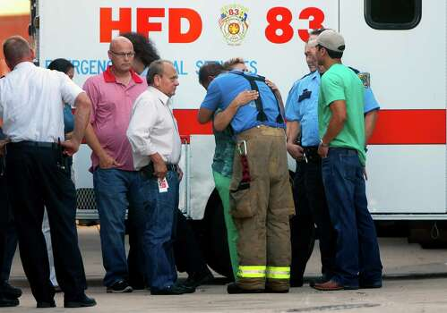 Friends and family hug outside of the Forensic Center of Harris County after the bodies of the four fallen firefighters were taken to be examined, Friday, May 31, 2013, in Houston. The firefighters died fighting a five-alarm fire at the Southwest Inn earlier in the day. Photo: Cody Duty, Houston Chronicle / © 2013 Houston Chronicle