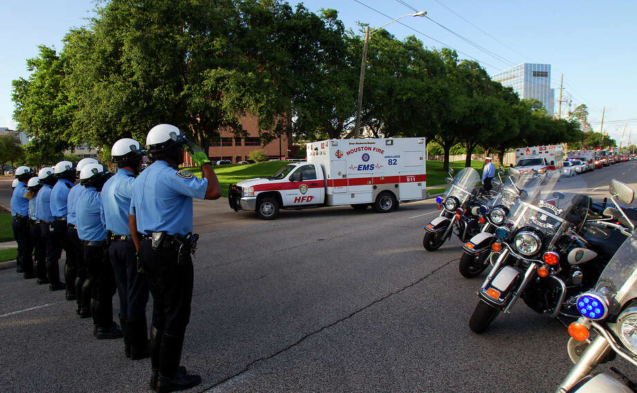 Police salute as an ambulance carrying the body of a fallen firefighter drives into the Forensic Center of Harris County to be examined, Friday, May 31, 2013, in Houston. The firefighters died fighting a five-alarm fire at the Southwest Inn earlier in the day. Photo: Cody Duty, Houston Chronicle / © 2013 Houston Chronicle