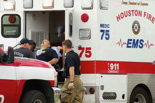 A Houston firefighter is loaded into an ambulance near the scene a fatal five-alarm fire at a motel on the Southwest Freeway Friday, May 31, 2013, in Houston. Photo: Brett Coomer, Houston Chronicle / © 2013 Houston Chronicle