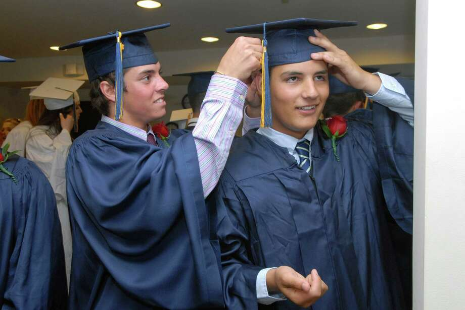Anthony DeLuca gets help from Andy Farber puuting on his cap for KIng Low Heywood Thomas high school graduation commencement in Stamford, Conn. on Friday May 31, 2013. Photo: Dru Nadler / Stamford Advocate Freelance