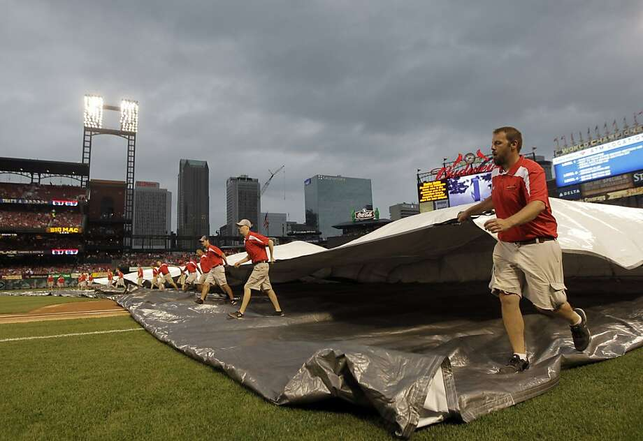 Members of the grounds crew put the tarp on the field before the game, which was rained out. Photo: Jeff Roberson, Associated Press