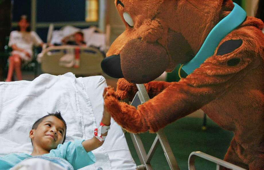 Marcus Martinez, 7, of Rosenberg gets a high-five from Scooby-Doo at Children's Memorial Hermann Hospital during a story-time visit from characters Shaggy and Scooby-Doo Friday, May 31, 2013, in Houston. 