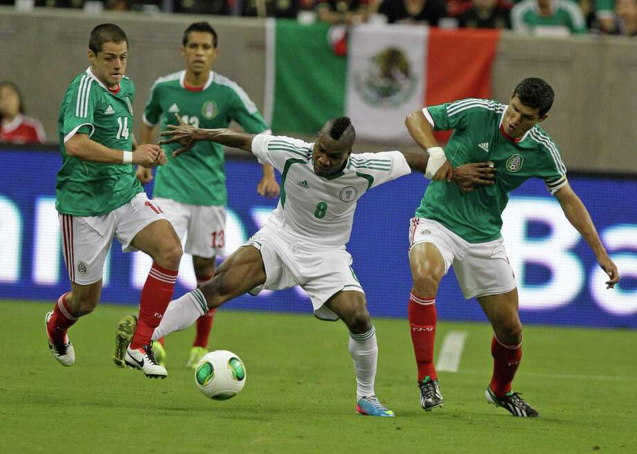 Nigeria player Aide Brown Ideye, center, works to control ball against Mexico players Javier Hernandez, left, Severo Meza, second from left, and Francisco Rodriguez, right, during first half of soccer match at Reliant Stadium Friday, May 31, 2013, in Houston. Photo: Melissa Phillip, Houston Chronicle / © 2013  Houston Chronicle
