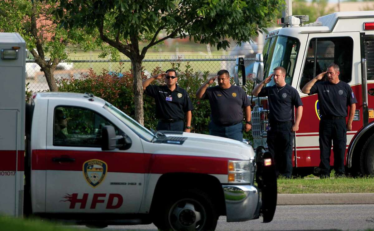 Firefighters salute as a procession carrying the bodies of the four fallen firefighters drives to the Forensic Center of Harris County on Friday.