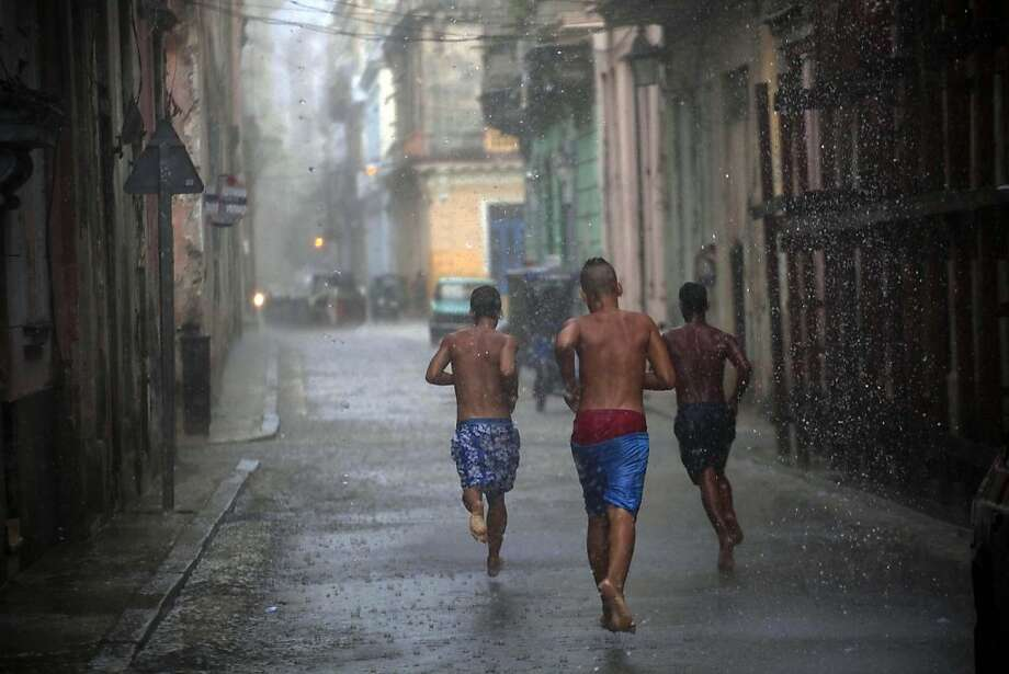 Boys compete in a foot race through the streets of  Old Havana, Cuba, during a rain shower Friday, May 31, 2013. An extended two week forecast predicts rains and thunderstorms for the Caribbean island. (AP Photo/Ramon Espinosa) Photo: Ramon Espinosa, Associated Press