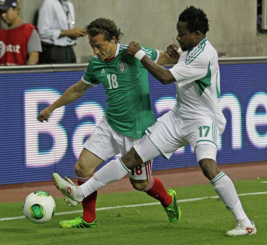 Mexico player Andres Guardado, left, battles Nigeria player Ogenyi Onazi, right,  for the ball during first half of soccer match at Reliant Stadium Friday, May 31, 2013, in Houston. Photo: Melissa Phillip, Houston Chronicle / © 2013  Houston Chronicle