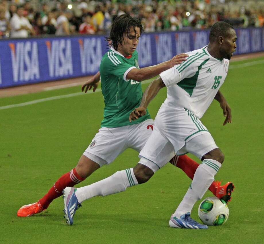 Mexico player Jesus Coronda, left, works to get ball from Nigeria player Obinna Nwachukwu, right, during second half of soccer match at Reliant Stadium Friday, May 31, 2013, in Houston. Photo: Melissa Phillip, Houston Chronicle / © 2013  Houston Chronicle