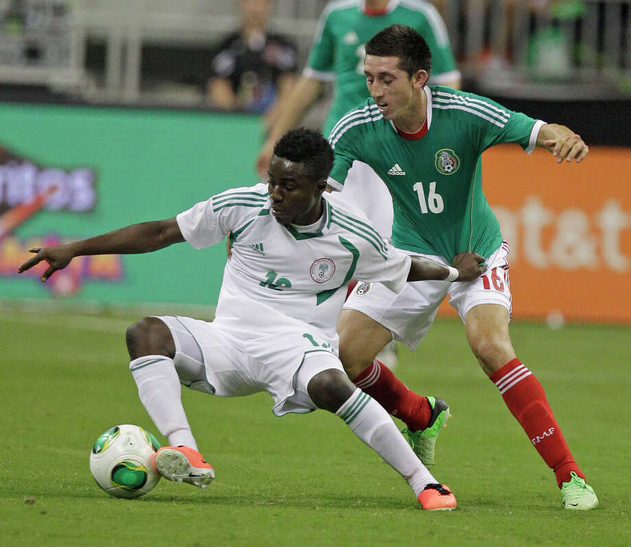 Nigeria player Ezeh Emea, left, works to control ball ahead of Mexico player Hector Herrera, right,  during second half of soccer match at Reliant Stadium Friday, May 31, 2013, in Houston. Photo: Melissa Phillip, Houston Chronicle / © 2013  Houston Chronicle