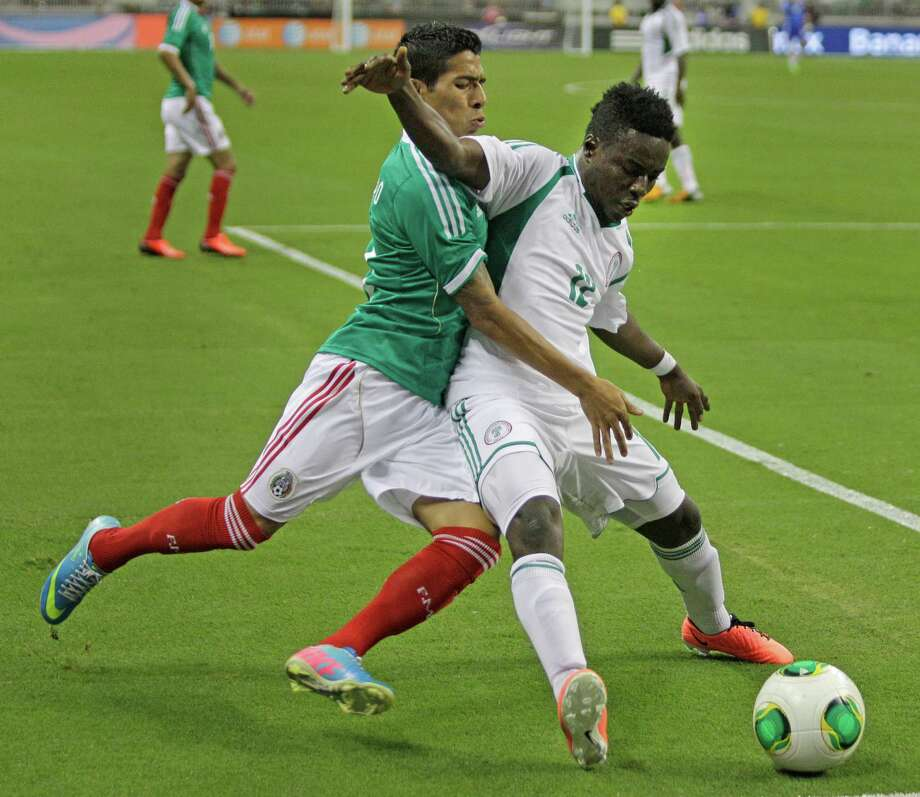 Mexico player Javier Aquino, left, and Nigeria player Ezeh Emeka battle for the ball during second half of soccer match at Reliant Stadium Friday, May 31, 2013, in Houston. Photo: Melissa Phillip, Houston Chronicle / © 2013  Houston Chronicle