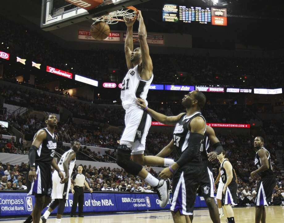 Spurs' Tim Duncan (21) dunks against Sacramento Kings' Marcus Thornton (23) in the first quarter at the AT&T Center on Friday, Apr. 12, 2013.