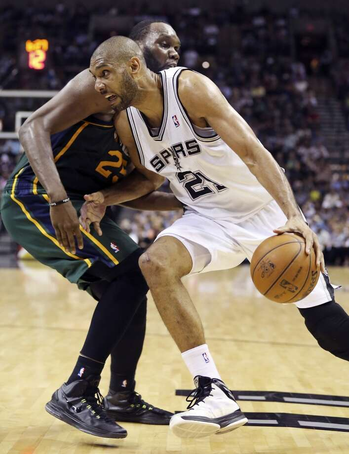 San Antonio Spurs' Tim Duncan looks for room around Utah Jazz's Al Jefferson during second half action Friday March 22, 2013 at the AT&T Center. The Spurs won 104-97 in overtime.
