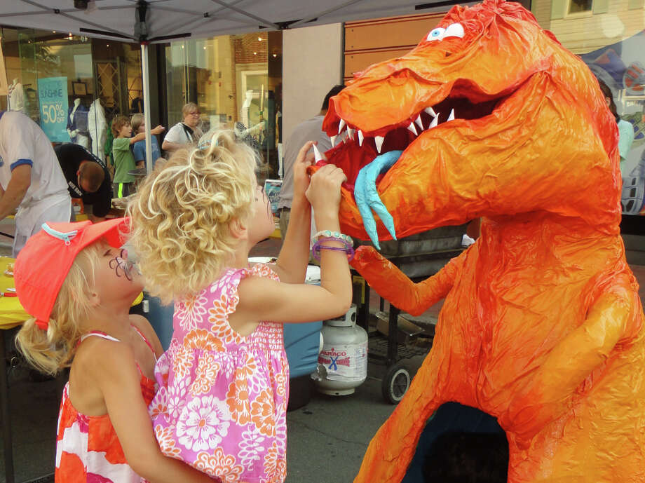 Cameron Cooleen, 5, lifts her twin sister Caleigh to get a look into the mouth of the dragon sculpture on Main Street during Thursday's Art About Town street party, organized by the Downtown Merchants Association. Caleigh returned the favor for her sister, and both girls also sat inside the dragon. Photo: Meg Barone / Westport News contributed