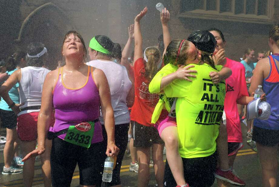 Saga Convoy, right, of Castleton gets a hug from her six-year-old daughter Kamilla Convoy as the two cool off in the spray from a fire hose after both completing the 35th annual Freihofer's Run for Women on Saturday June 1, 2013 in Albany, N.Y.  (Michael P. Farrell/Times Union) Photo: Michael P. Farrell