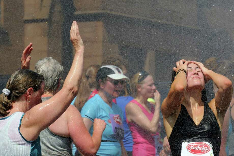 Runners cool off in a mist off water after competing in the 35th annual Freihofer's Run for Women on Saturday June 1, 2013 in Albany, N.Y.  (Michael P. Farrell/Times Union) Photo: Michael P. Farrell
