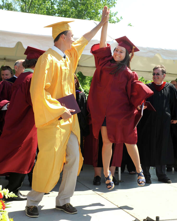 Sophia DeBroff, of Trumbull, jumps to high five fellow graduate Steven D'Ascanio, of Trumbull, during graduation for the St. Joseph High School Class of 2013, in Trumbull, Conn., June 1st, 2013 Photo: Ned Gerard / Connecticut Post