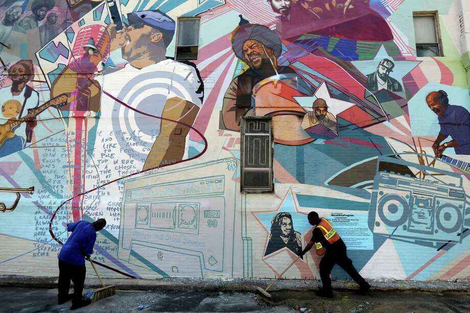 "Workmen sweep in front of a new mural honoring The Roots, Friday, May 31, 2013, in Philadelphia. As a teen growing up in Philadelphia, Tariq ""Black Thought"" Trotter got busted for graffiti and was ordered by a judge to clean up such vandalism by painting murals. Now, Trotter and his Grammy-winning band The Roots are scheduled to attend Friday the unveiling of a city-sanctioned mural in their honor.  (AP Photo/Matt Rourke) Photo: Matt Rourke"