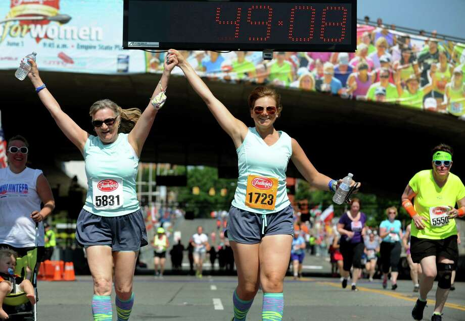 Charlene Hoffay of Averill Park, left, and her daughter Erin Hoffay cross the finish line together during the 35th annual Freihofer's Run for Women on Saturday, June 1, 2013, in Albany, N.Y. (Cindy Schultz / Times Union) Photo: Cindy Schultz / 00022653A