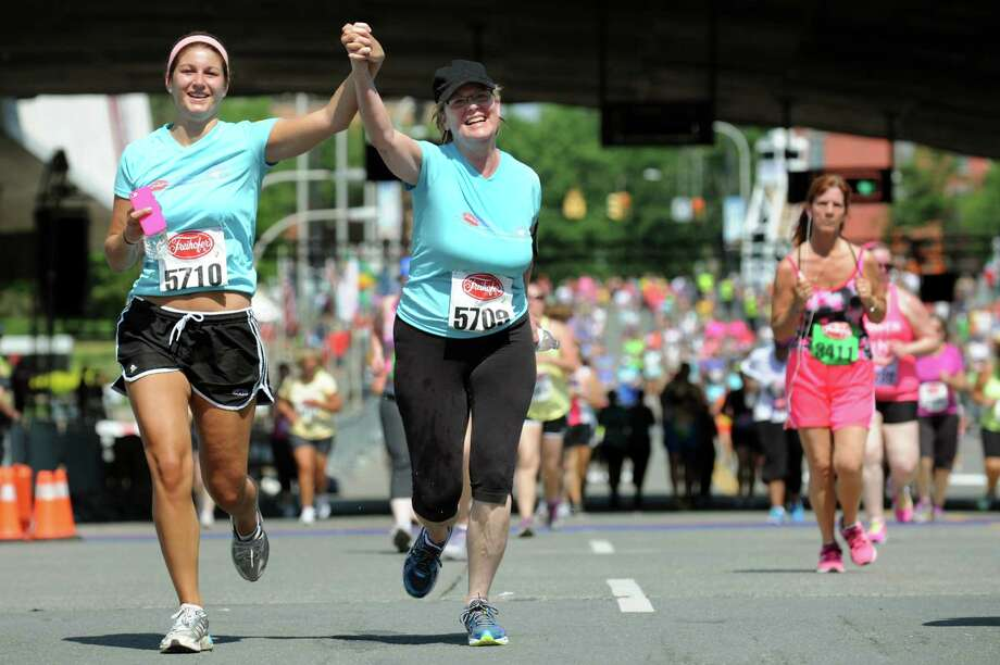 Kelsie Harris of East Greenbush, left, and her mother Marianne Harris cross the finish line together during the 35th annual Freihofer's Run for Women on Saturday, June 1, 2013, in Albany, N.Y. (Cindy Schultz / Times Union) Photo: Cindy Schultz / 00022653A