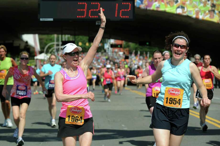 Friends Donna Lustenhouwer of Altamont, center, and Diana Steenburg of Albany, right, celebrate at the finish line together during the 35th annual Freihofer's Run for Women on Saturday, June 1, 2013, in Albany, N.Y. (Cindy Schultz / Times Union) Photo: Cindy Schultz / 00022653A