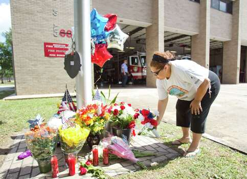 Mildred Lozano places flowers on a makeshift memorial honoring the lives of four fallen firefighters outside Houston Fire Station 68 Saturday, June 1, 2013, in Houston. Four HFD firefighters died Friday battling a 5-alarm fire at the Southwest Inn. Photo: Brett Coomer, Houston Chronicle / © 2013 Houston Chronicle