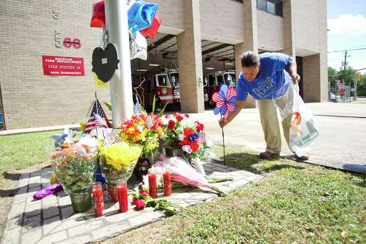 Sancha Buckner adds a red, white and blue pinwheel to a makeshift memorial honoring the lives of four fallen firefighters outside Houston Fire Station 68 Saturday, June 1, 2013, in Houston. Four HFD firefighters died Friday battling a 5-alarm fire at the Southwest Inn. Photo: Brett Coomer, Houston Chronicle / © 2013 Houston Chronicle