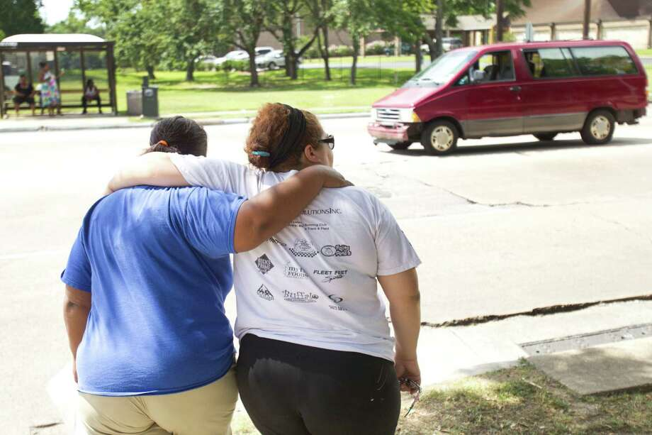 Sancha Buckner, left, and Mildred Lozano embrace as they walk away from Houston Fire Station 68 Saturday, June 1, 2013, in Houston. Bucker and Lozano added to a makeshift memorial outside the station to the four HFD firefighters who died Friday battling a 5-alarm fire at the Southwest Inn. Photo: Brett Coomer, Houston Chronicle / © 2013 Houston Chronicle
