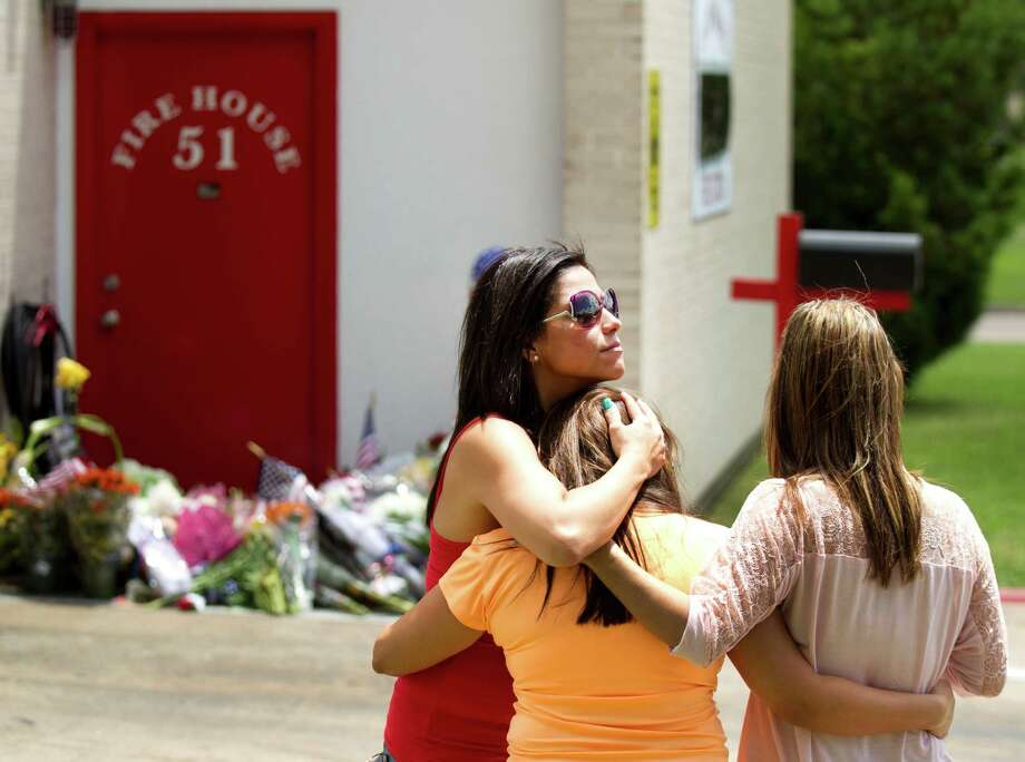 """Yolanda Ramos, left, Erica Hernandez and Michelle Rico embrace after they places flags and flowers onto a makeshift memorial honoring four fallen firefighters outside Houston Fire Station 51 Saturday, June 1, 2013, in Houston. Hernandez, who was a friend of fallen firefighter, Capt. Matthew Renaud, 35, said, """"He died doing what he loved."""" Renaud was one of four HFD firefighters who died battling a 5-alarm fire at a motel along the Southwest Freeway. Photo: Brett Coomer, Houston Chronicle / © 2013 Houston Chronicle"""