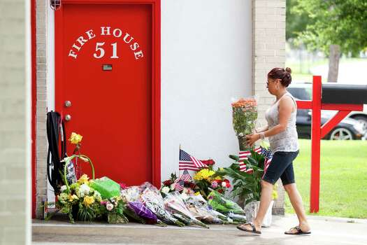 A woman brings flowers to Houston Fire Station 51 as a makeshift memorial grows outside the station Saturday, June 1, 2013, in Houston. People continued to stop by Station 51 Saturday to honor the lives of the four Houston firefighters who perished battling a 5-alarm blaze at the Southwest Inn on Friday. Photo: Brett Coomer, Houston Chronicle / © 2013 Houston Chronicle
