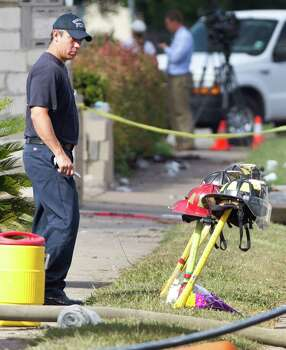 A firefighter pauses near four fire helmets placed in front of the Southwest Inn as the investigation into a 5-alarm fire continues Saturday, June 1, 2013, in Houston. The helmets honor the lives of the four Houston firefighters who perished battling a 5-alarm fire Friday. Photo: Brett Coomer, Houston Chronicle / © 2013 Houston Chronicle