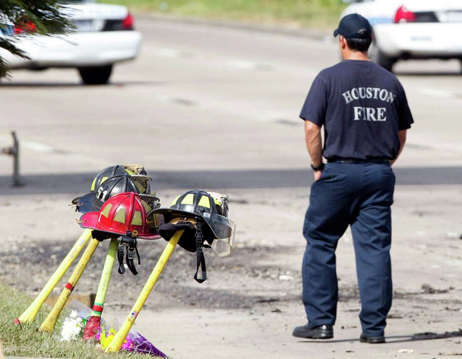 A firefighter walks past four fire helmets placed in front of the Southwest Inn as the investigation into a 5-alarm fire continues Saturday, June 1, 2013, in Houston. The helmets honor the lives of the four Houston firefighters who perished battling a 5-alarm fire Friday. Photo: Brett Coomer, Houston Chronicle / © 2013 Houston Chronicle
