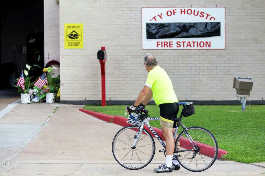 A man pauses in front of Houston Fire Station 51 as a makeshift memorial grows outside there station Saturday, June 1, 2013, in Houston. People continued to stop by Station 51 Saturday to honor the lives of the four Houston firefighters who perished battling a 5-alarm blaze at the Southwest Inn on Friday. Photo: Brett Coomer, Houston Chronicle / © 2013 Houston Chronicle