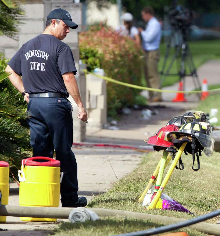 A firefighter pauses near four fire helmets placed in front of the Southwest Inn as the investigation into a 5-alarm fire continues Saturday, June 1, 2013, in Houston. The helmets honor the lives of the four Houston firefighters who perished battling a 5-alarm fire Friday.  Among the four killed were veterans of the department and a newcomer just a month out of the fire training academy. The fire broke out at a restaurant connected to the Southwest Inn along a busy freeway, and was the deadliest in the 118-year history of the department. Three firefighters died at the scene, while the fourth died at a hospital, according to the mayor's office and a medical examiner. (AP Photo/Houston Chronicle, Brett Coomer)    MANDATORY CREDIT Photo: Brett Coomer, Associated Press / Houston Chronicle