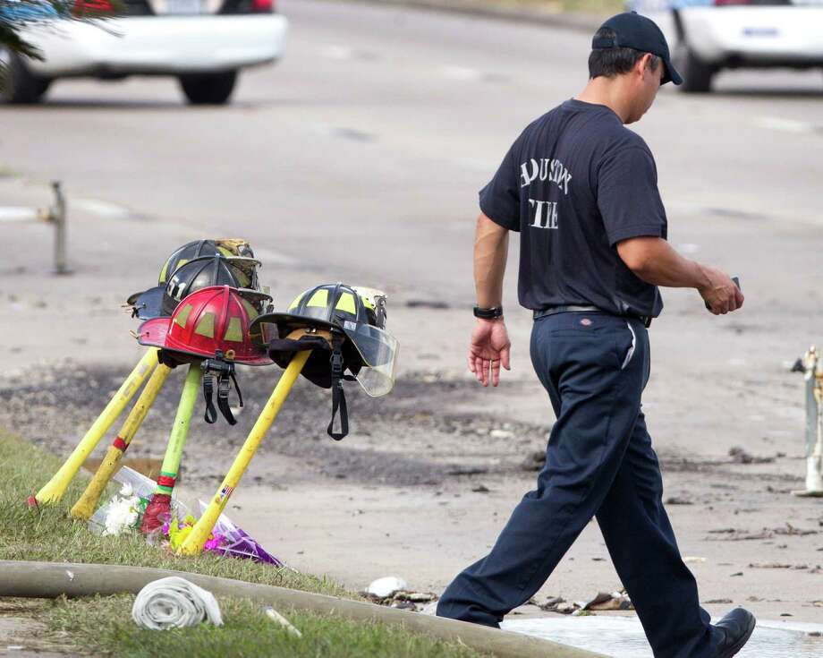 A firefighter walks past four fire helmets placed in front of the Southwest Inn as the investigation into a 5-alarm fire continues Saturday, June 1, 2013, in Houston. The helmets honor the lives of the four Houston firefighters who perished battling a 5-alarm fire Friday.  Among the four killed were veterans of the department and a newcomer just a month out of the fire training academy. The fire broke out at a restaurant connected to the Southwest Inn along a busy freeway, and was the deadliest in the 118-year history of the department. Three firefighters died at the scene, while the fourth died at a hospital, according to the mayor's office and a medical examiner. (AP Photo/Houston Chronicle, Brett Coomer)    MANDATORY CREDIT Photo: Brett Coomer, Associated Press / Houston Chronicle