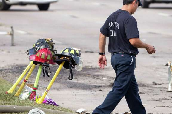 A firefighter walks past four fire helmets placed in front of the Southwest Inn as the investigation into a 5-alarm fire continues Saturday, June 1, 2013, in Houston. The helmets honor the lives of the four Houston firefighters who perished battling a 5-alarm fire Friday.  Among the four killed were veterans of the department and a newcomer just a month out of the fire training academy. The fire broke out at a restaurant connected to the Southwest Inn along a busy freeway, and was the deadliest in the 118-year history of the department. Three firefighters died at the scene, while the fourth died at a hospital, according to the mayor's office and a medical examiner. (AP Photo/Houston Chronicle, Brett Coomer)    MANDATORY CREDIT