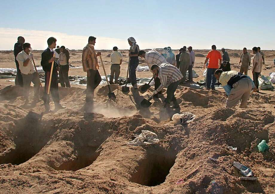 In this Friday, Nov. 10, 2006 file photo, Iraqi volunteers bury bodies in the Shiite holy city of Najaf, 160 kilometers (100 miles) south of  Baghdad, Iraq as 176 bodies of victims of recent sectarian violence were brought from Baghdad to Najaf for the funeral. More than a year after the U.S. military left Iraq, the country is reeling from its most sustained violence since 2008. Over the last two months more than 1,200 people have been killed, raising fears the country is sliding back into chaos. (AP Photo/Alaa al-Marjani, File) Photo: Alaa Al-Marjani, Associated Press