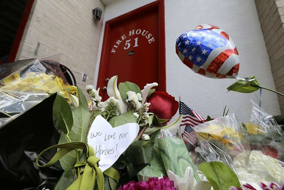 A note attached to flowers at a memorial outside Houston Fire Station 51 pays tribute to the four who died. Photo: David J. Phillip, Associated Press
