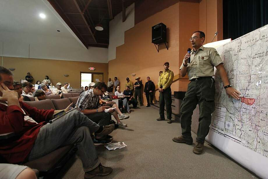 Robert Morales, with the Santa Fe National Forest, speaks at a community meeting at Pecos High School to update residents on the fire situation on May 31, 2013 in Pecos, N.M.  Officials said the fire in New Mexico's Santa Fe National Forest more than doubled in size by Friday night and was still totally uncontained. That prompted New Mexico Gov. Susana Martinez to declare a state of emergency in San Miguel County to free up state funds to fight the fire.  (AP Photo/The Santa Fe New Mexican, Luis Sanchez Saturno) Photo: Luis SÁnchez Saturno, Associated Press