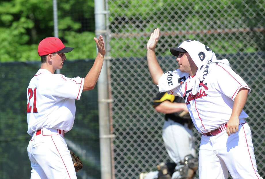 At left, Greenwich pitcher J.T. Hintzen of Greenwich gets a high-five from teammate Michelangelo Federici during the Class LL baseball quarterfinal game between Greenwich High School and Amity High School at Greenwich, June 1, 2013. Amity defeated Greenwich 6-0 as Amity pitcher Michael Concato threw a no hitter. Photo: Bob Luckey / Greenwich Time