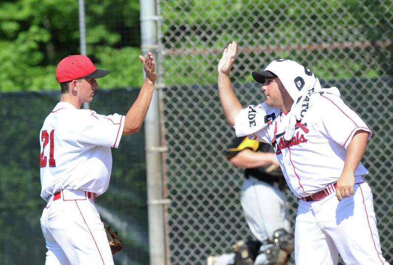 At left, Greenwich pitcher J.T. Hintzen of Greenwich gets a high-five from teammate Michelangelo Fed
