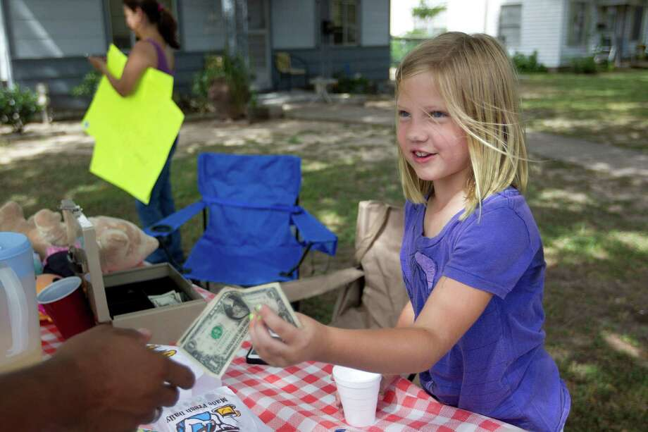 Avery Brown, 7, collect money at her lemonade stand in the Oak Forest neighborhood that she and a friend, Cristina McInnis, 7, organized to collect money to give to the local fire department after four fighters died in a 5-alarm fire Friday, Saturday, June 1, 2013, in Houston.  The $185 donations went to their local fire stations, Station 13 and 31. Photo: Johnny Hanson, Houston Chronicle / © 2013  Houston Chronicle