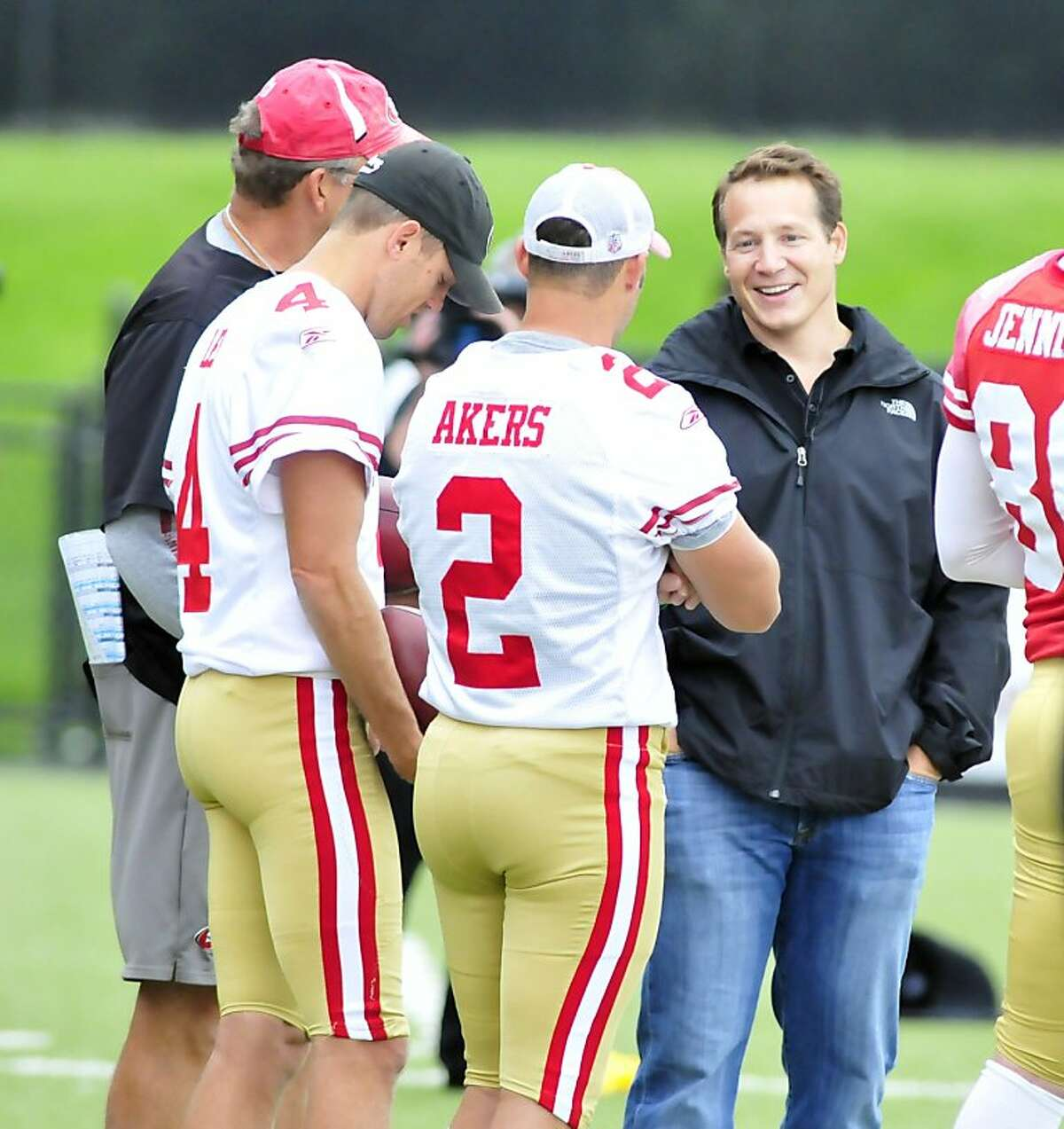 YOUNGSTOWN, OHIO - SEPTEMBER 29, 2011: Former head coach Eric Mangini of the New York Jets and Cleveland Browns smiles while talking with kicker David Akers #2 and punter Andy Lee #4 of the San Francisco 49ers during practice at Stambaugh Stadium at Youngstown State University in Youngstown, Ohio on September 29, 2011. (Photo by David Dermer/Diamond Images/Getty Images)